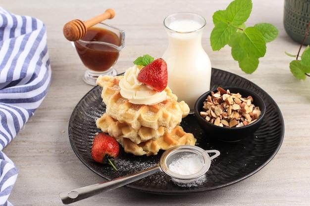 メープルシロップ、刻んだアーモンド、シュガーダスティング、ストロベリーを添えた焼きたてのおいしい自家製クロワッサンワッフルまたはクロワッフル。朝食のための簡単な作り
