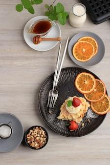 メープルシロップ、みじん切りアーモンド、ストロベリーを添えた焼きたてのおいしい自家製クロワッサンワッフル。
