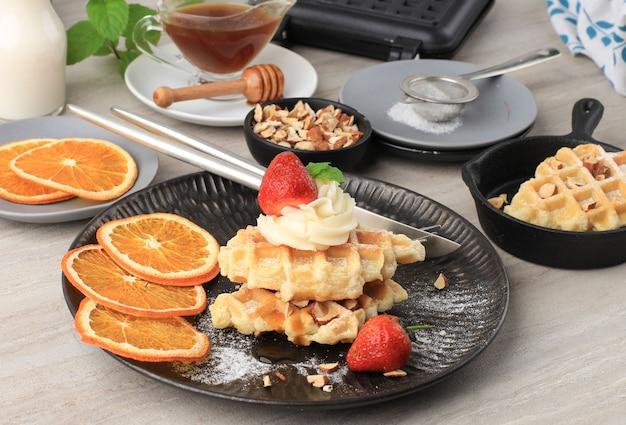 メープルシロップ、みじん切りアーモンド、ドライオレンジ、ストロベリーを添えた焼きたてのおいしい自家製クロワッサンワッフル。シュガーダスティングを添えたブラックドフプレートでお召し上がりいただけます