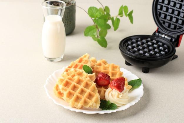 Свежие запеченные вкусные домашние вафли из круассанов с клубникой и молоком на завтрак. подается на белой тарелке, крем чистый фон для рекламы.