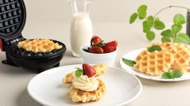 Свежие испеченные вкусные домашние вафли из круассана с клубникой. подается на белой тарелке, крем чистый фон для рекламы. подается на белой тарелке с молоком, клубникой и листом мяты