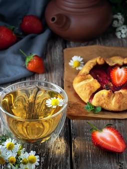 テーブルの上の焼きたてのガレットパイとカモミールティーのカップ