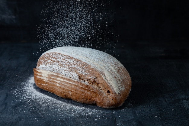 Fresh baked gluten-free grey bread. fresh bread on table close-up. food in motion concept. flour fly on bread in kicthen. eco food. sprinkling, flying flour. bakery concept