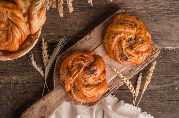 焼きたての商品、木製の背景にケシの実とおいしい籐のパン