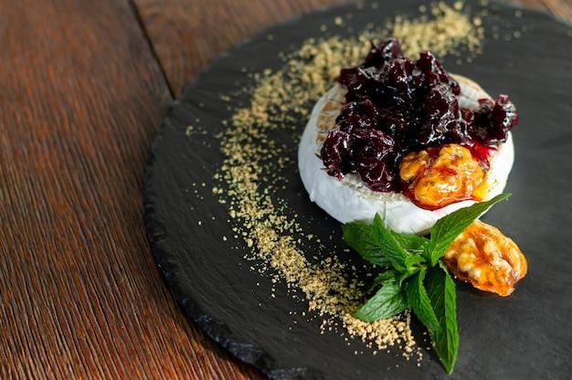 Свежий запеченный камамбер на гриле с клюквенным соусом, зеленью и карамелизированными грецкими орехами крупным планом