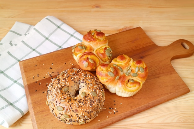 Fresh baked homemade buns with pumpkin seed and sesame on a wooden breadboard
