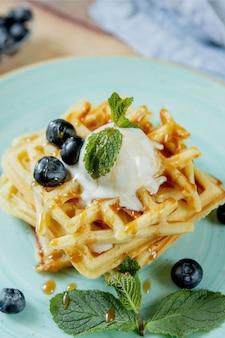 Свежие испеченные домодельные классические бельгийские вафли покрытые с мороженым, свежими голубиками и мятой на деревянном столе, верхний взгляд вниз. пикантные вафли. концепция завтрака