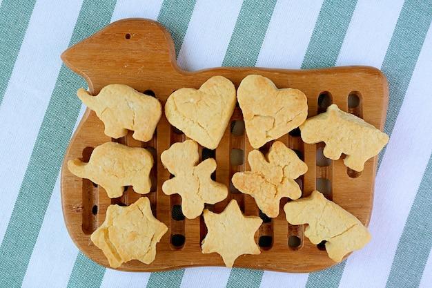 신선한 구운 수제 사랑스러운 모양의 버터 쿠키가 나무 오리 새 브레드 보드에서 냉각되고