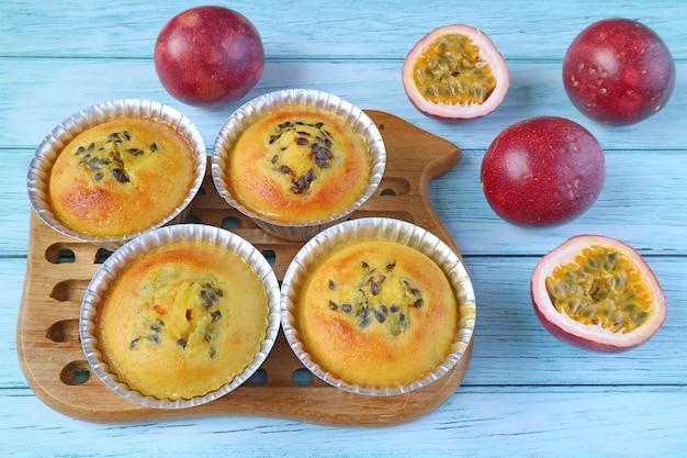 ブレッドボードの型に焼きたての自家製パッションフルーツマフィンと淡いブルーのテーブルに散らばった新鮮なフルーツ
