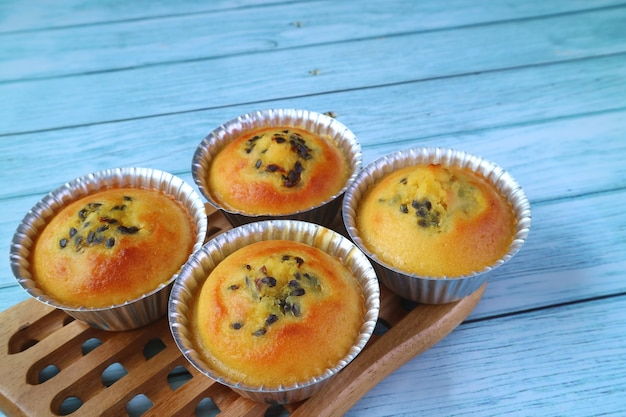 Fresh baked homemade passion fruit muffins in molds on wooden breadboard