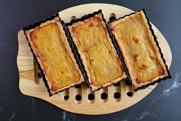 Fresh baked homemade pumpkin tartlets on the wooden breadboard