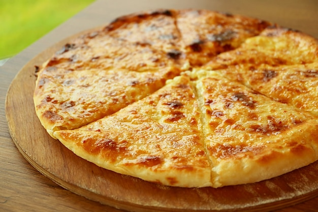 나무 접시에 갓 구운 카차푸리 이메룰리 이메레티안 또는 치즈로 채워진 그루지야 플랫브레드