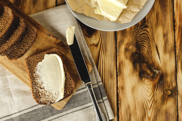 木製のテーブルにバターバーと焼きたてのパンのパン