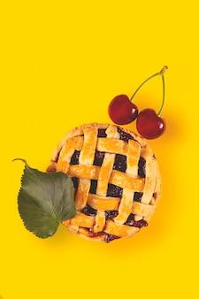 焼きたてのミニチェリーパイは、熟したサクランボと黄色の紅葉を使った秋の自家製料理です