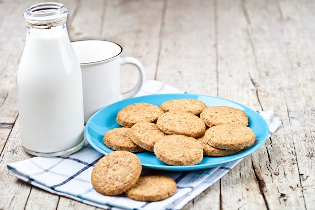 Fresh baked oat cookies on blue ceramic plate on linen napkin, bottle of milk and ceramic cup