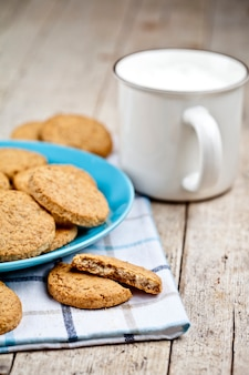 Fresh baked oat cookies on blue ceramic plate on linen napkin and cup of milk.