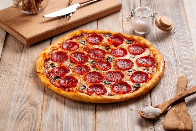 木製のテーブルにサラミとオリーブを添えた焼きたてのペパロニピザ
