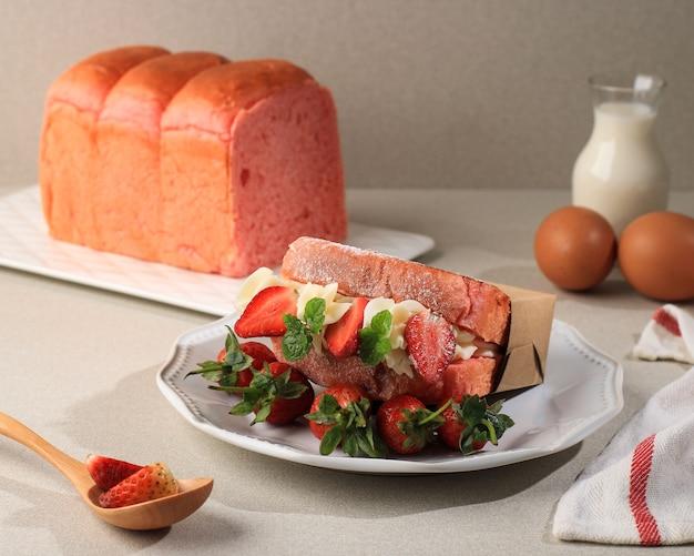 クリームチーズとイチゴのサンドイッチ用の焼きたてのピンクのパン、クリーム色の背景、広告のためのきれいなスタイリング