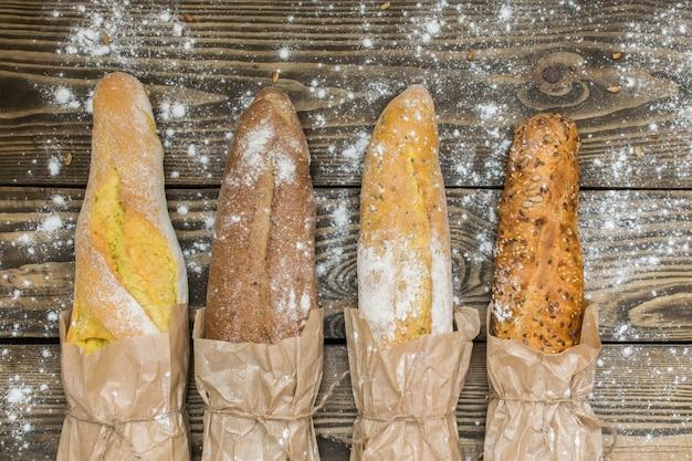 어두운 나무 테이블에 종이 봉투에 신선한 구운 소박한 빵 덩어리