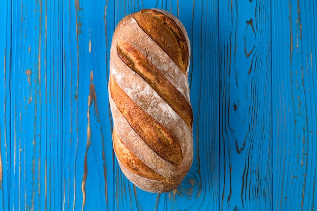 Fresh baked rye bread on a blue wooden background.