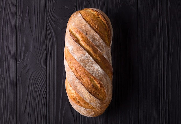 Fresh baked rye bread isolated on a black wooden table.