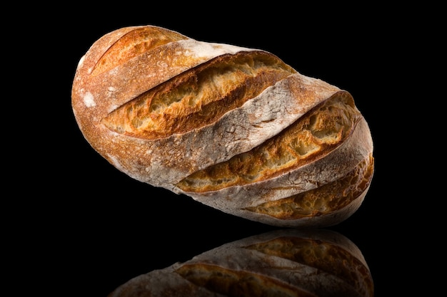 Fresh baked rye bread with reflection isolated on a black background.