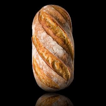 黒の背景に分離された反射と焼きたてのライ麦パン。