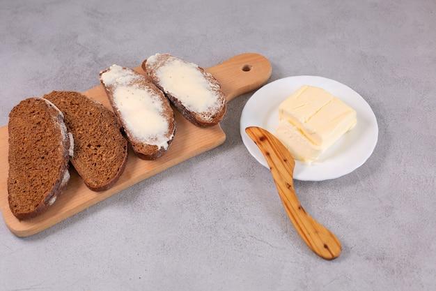 나무 커팅 보드에 버터를 얹은 갓 구운 얇게 썬 장인 빵