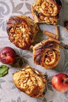 Свежее запеченное сладкое яблоко липкие булочки с корицей булочки с садовыми яблоками и палочками корицы на декоративном фоне керамической плитки. традиционная домашняя выпечка