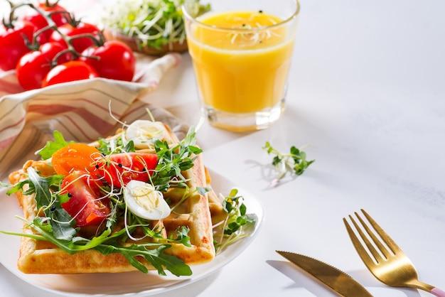 Свежеиспеченные сладкие бельгийские вафли с яйцами, помидорами, микро зеленью и авокадо, подаются на тарелке с апельсиновым соком на мраморе