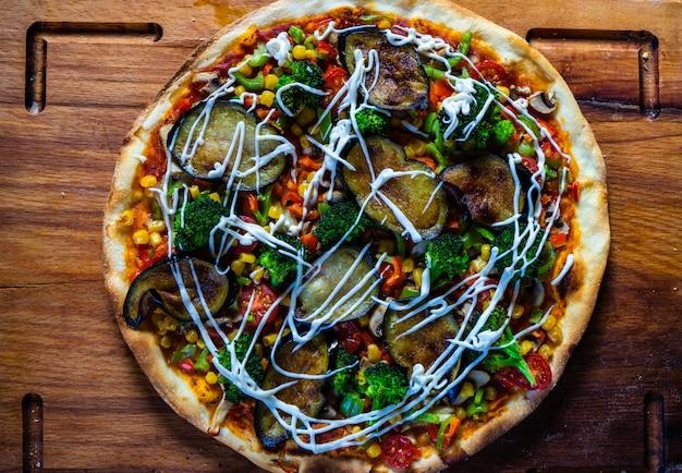 木の板に焼きたてのベジタリアンピザ