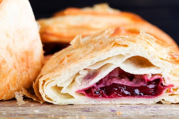 小麦粉パンの詰め物として熟した赤いチェリーベリーで焼きたて