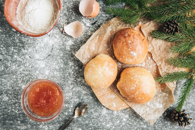 Fresh baked yeast buns filled with apple jam on gray background with flour.