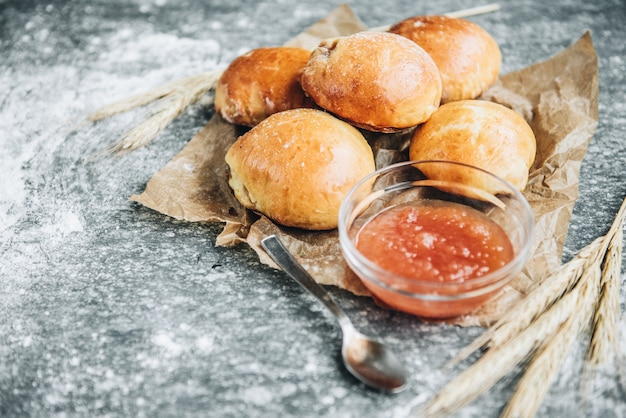 Fresh baked yeast buns filled with apple jam on gray surface with flour.
