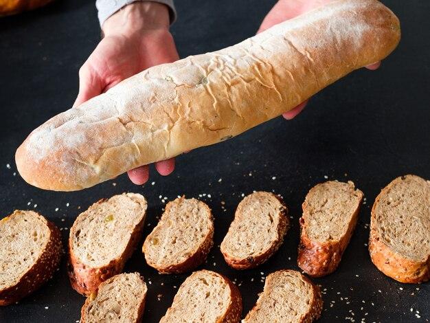 신선한 빵집. 사업 시작. wholegrain 빵 조각 위에 바게트를 들고 손입니다.