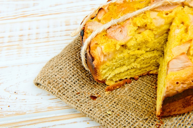 Fresh bakery. close-up of baked pie with apples on sackcloth on a white wooden. rustic style.