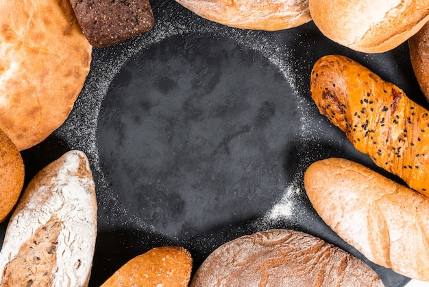 Fresh bakery food, rustic crusty loaves of bread on black stone background. top view