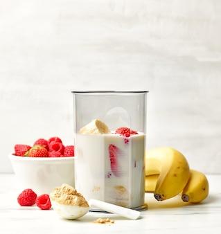 식탁에서 건강한 아침 식사 밀크셰이크를 만들기 위한 믹서기 용기에 신선한 바나나, 딸기, 우유