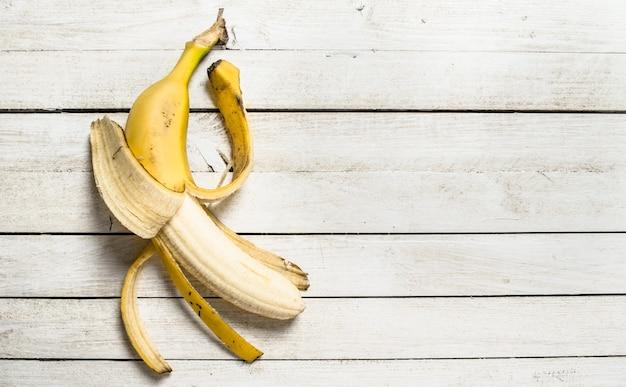 Свежий банан на белом деревянном столе.