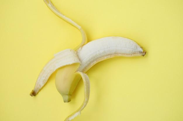 노란색 배경에 신선한 바나나입니다. 바나나와 함께 완벽 한 패턴입니다. 열 대 추상적인 배경입니다. 노란색 배경에 바나나입니다. 노란색 배경에 껍질을 벗긴 바나나 프리미엄 사진