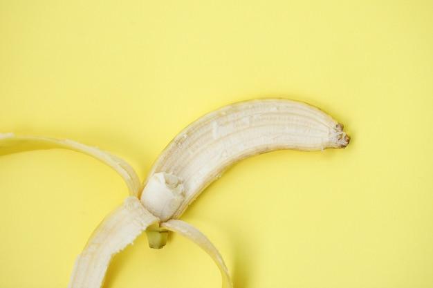 노란색 배경에 신선한 바나나입니다. 바나나와 함께 완벽 한 패턴입니다. 열 대 추상적인 배경입니다. 노란색 배경에 바나나입니다. 노란색 배경에 껍질을 벗긴 바나나