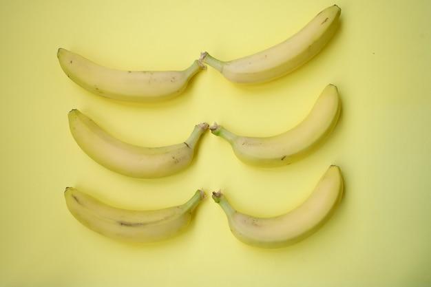 노란색 배경에 신선한 바나나입니다. 바나나와 함께 완벽 한 패턴입니다. 열 대 추상적인 배경입니다. 노란색 배경에 바나나