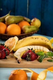Fresh banana,orange and strawberries on a wooden board