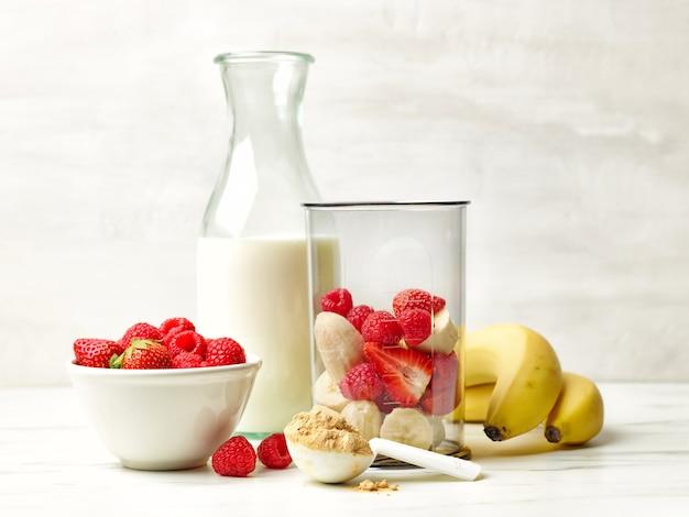 건강한 아침 식사 스무디를 만들 준비가 된 식탁에 있는 플라스틱 투명 블렌더 용기와 우유 병에 신선한 바나나 조각과 붉은 열매