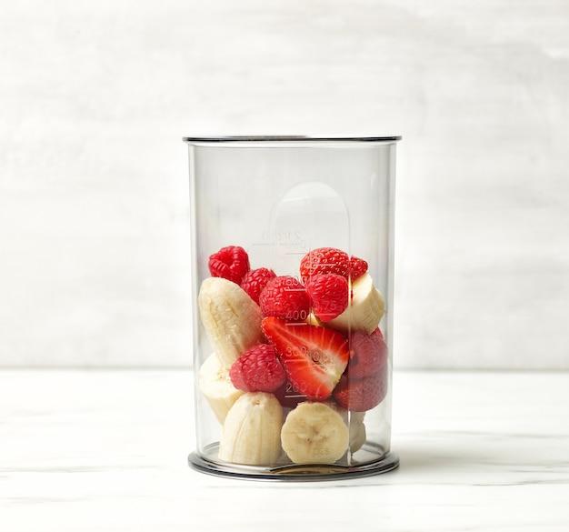 건강한 아침 식사 스무디를 만들 준비가 된 식탁에 있는 플라스틱 투명 블렌더 용기에 신선한 바나나 조각과 붉은 열매
