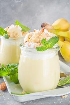 아침에는 신선한 바나나 푸딩, 바나나 요구르트. 바나나 조각과 견과류가 들어간 안경의 달콤한 디저트, 원시 채식 간식