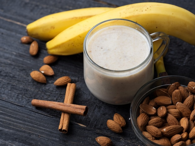 Fresh banana smoothie with almonds on a wooden background