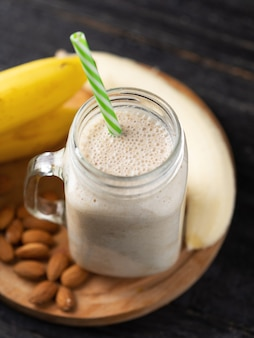 Fresh banana smoothie on a wooden table in a jar