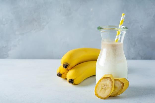 Свежие банановые смузи в стеклянной банке на светлом фоне бетона. здоровое питание, детокс, диетическое питание
