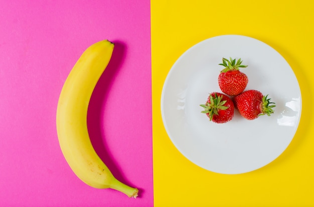 A fresh banana and strawberries lie on a yellow and pink surface